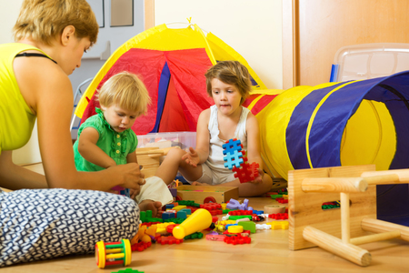 Young mother and children playing with toys in home: Delays in autism diagnosis threaten 'breakthrough' PACT treatment